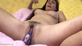 Mature woman inserts dildo in her hairy pierced pussy