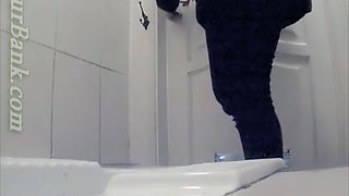 Pale skin white chick in black pants filmed from behind in the toilet