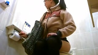 Asian women taking a leak in public toilet