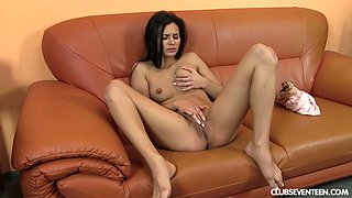 Brunette hottie enjoying a spicy solo pussy fingering session on the sofa