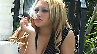 Girl in tight dress smokes outdoors